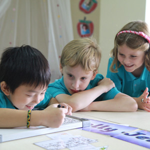 Three primary students in class working together