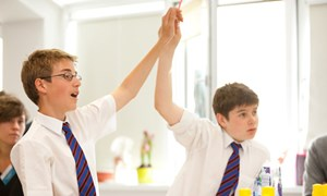 Students with hands in air to ask a question
