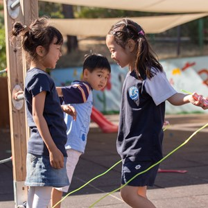 Primary school girls play with a skipping rope in the playground