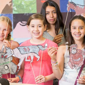 Grade 6 girls smile with puppets they have made in art class