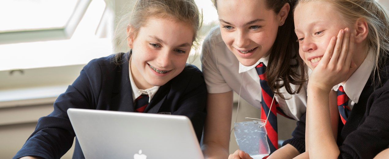 Three girls work together on a computer